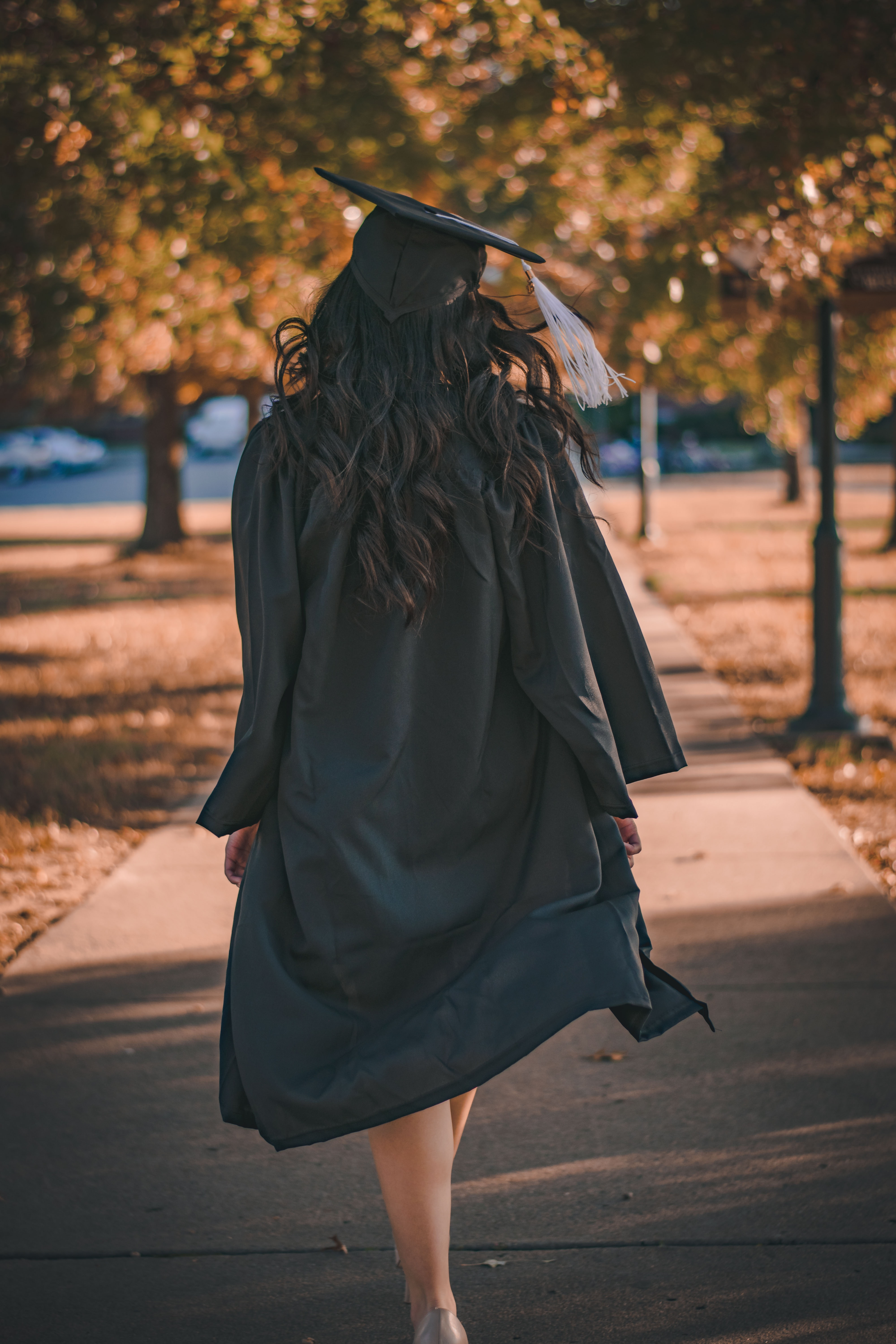 Student in graduating cap and gown with back turned to the camera.