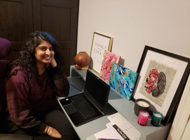Natasha sitting a her desk, which has her laptop, candles, and framed pictures and prints.