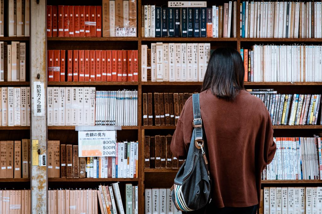 Person wearing a brown sweater looks through a bookstore.